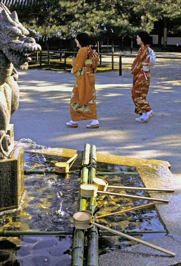 Geisha and traditional drinking fountain